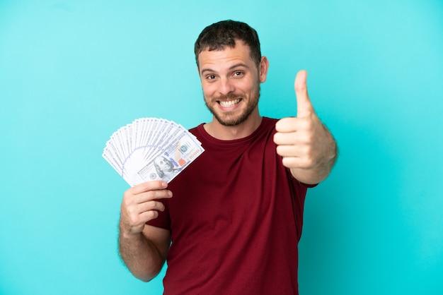 Jovem brasileiro ganhando muito dinheiro em um fundo isolado com o polegar levantado porque algo bom aconteceu