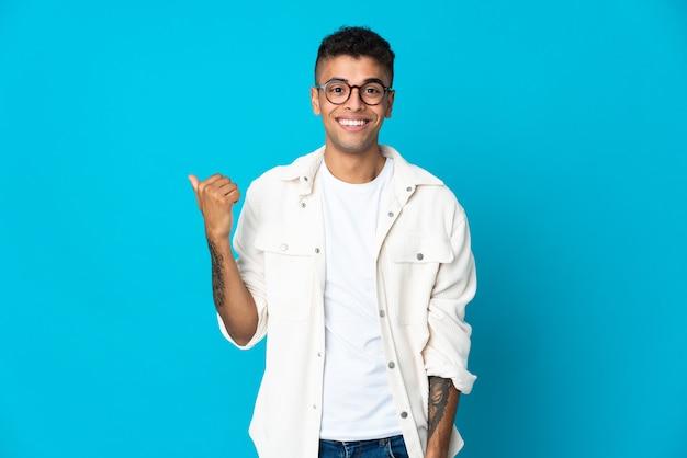 Jovem brasileiro isolado em parede azul apontando para a lateral para apresentar um produto