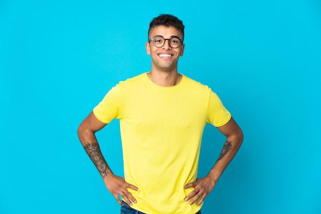 Jovem brasileiro isolado em uma parede azul posando com os braços na cintura e sorrindo