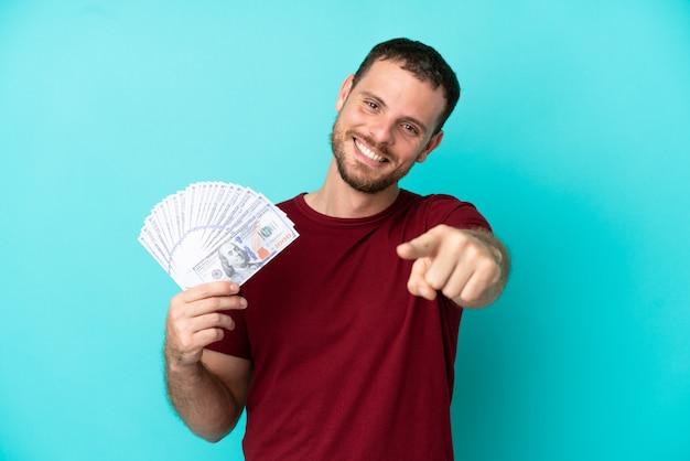 Jovem brasileiro levando muito dinheiro sobre um fundo isolado apontando para a frente com uma expressão feliz