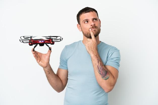 Jovem brasileiro segurando um drone isolado no fundo branco, tendo dúvidas enquanto olha para cima