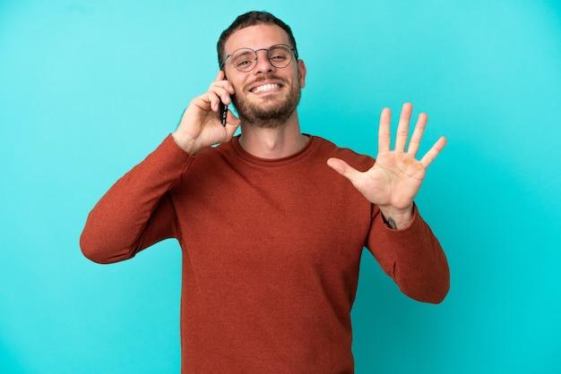 Jovem brasileiro usando celular isolado em fundo azul, contando cinco com os dedos