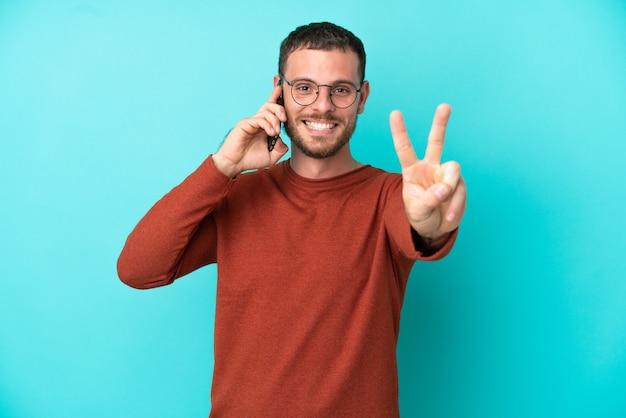 Jovem brasileiro usando celular isolado em fundo azul sorrindo e mostrando sinal de vitória