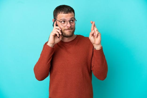 Jovem brasileiro usando celular isolado em um fundo azul, cruzando os dedos e desejando o melhor
