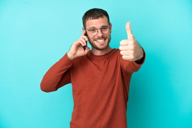 Jovem brasileiro usando telefone celular isolado em um fundo azul com polegar para cima porque algo bom aconteceu