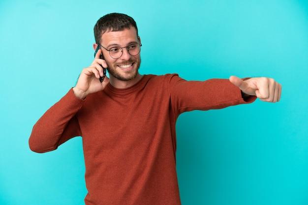 Jovem brasileiro usando um celular isolado em um fundo azul e fazendo um gesto de polegar para cima