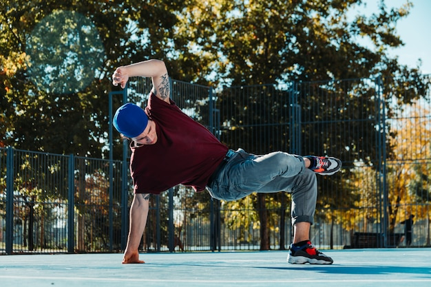 Jovem break dance na quadra de basquete