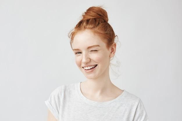 Jovem brincalhão mulher bonita com cabelo sexy, sorrindo piscando