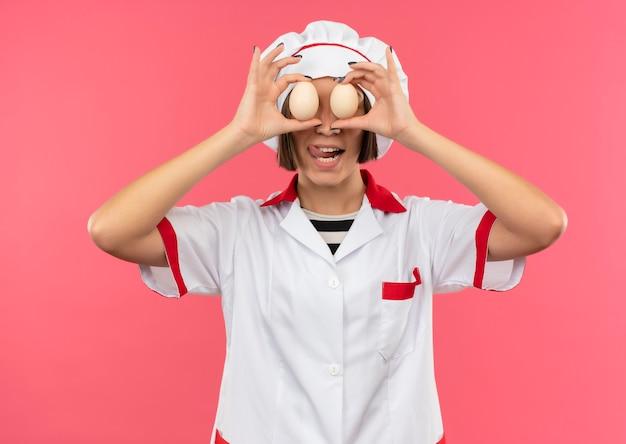 Jovem brincalhona cozinheira com uniforme de chef, colocando ovos nos olhos e mostrando a língua isolada no fundo rosa