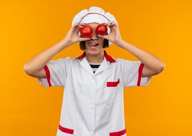 Jovem brincalhona cozinheira com uniforme de chef, colocando tomates nos olhos e mostrando a língua isolada em fundo laranja