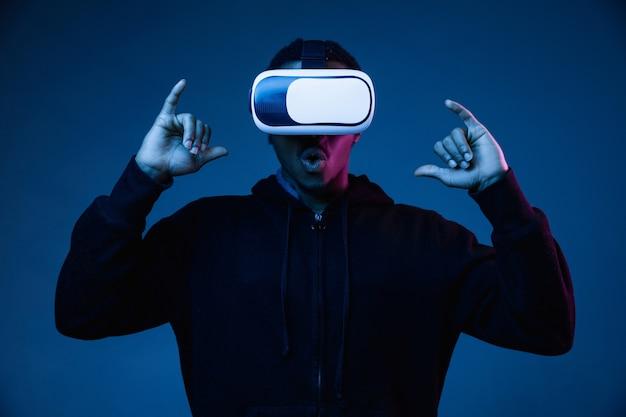 Jovem brincando com óculos de realidade virtual em luz de néon em gradiente