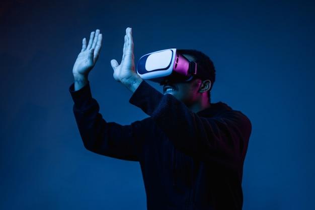 Jovem brincando com óculos de realidade virtual em luz de néon no azul