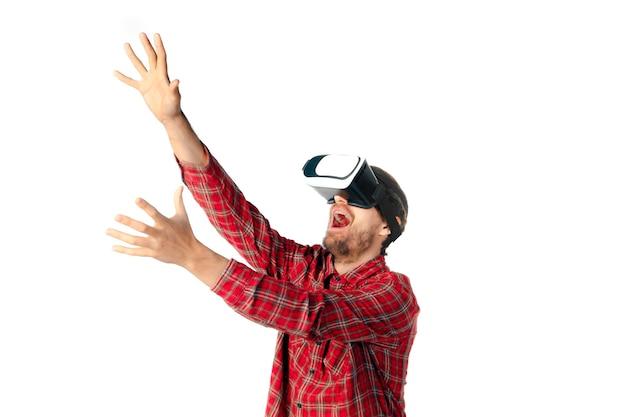 Jovem brincando com um fone de ouvido de realidade virtual isolado na parede branca do estúdio