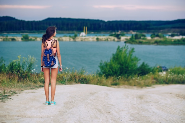 Jovem bronzeada linda viaja com uma mochila. andando sobre lagos.