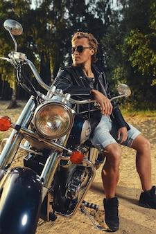 Jovem brutal de óculos escuros, jeans e jaqueta de couro preta sentado em uma motocicleta personalizada ao ar livre