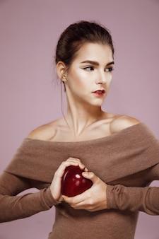 Jovem brutal segurando grande maçã vermelha nas mãos de rosa