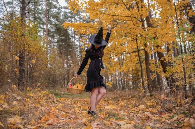 Jovem bruxa atraente caminha no conceito de forest.helloween de laranja de outono.