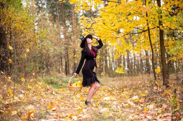 Jovem bruxa atraente caminha no conceito outono laranja silvestre