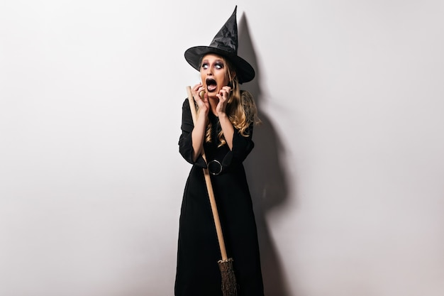 Jovem bruxa com chapéu, posando no halloween com expressão de rosto assustador. foto interna da modelo feminina loira chocada com fantasia de assistente.