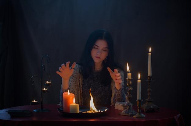 Jovem bruxa com fogo e velas acesas na superfície escura