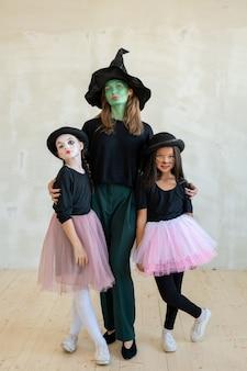 Jovem bruxa com o rosto pintado de verde abraçando duas meninas