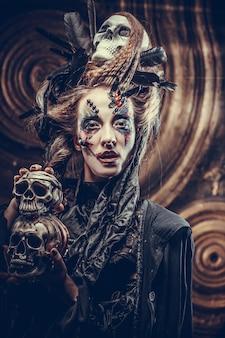 Jovem bruxa com uma caveira. tema brilhante de maquiagem e fumaça de halloween. tiro do estúdio.
