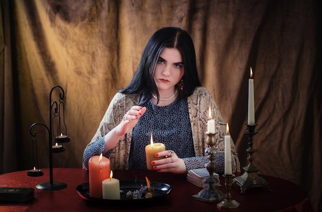 Jovem bruxa conjura velas acesas em fundo escuro