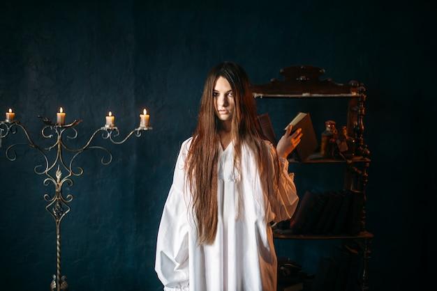 Jovem bruxa de camisa branca tem livro de feitiços nas mãos, velas. ritual de magia negra, ocultismo e exorcismo, bruxaria