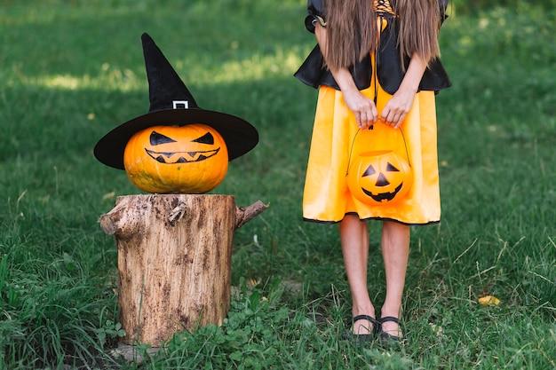 Jovem bruxa e jack-o-lanterna em pé na floresta no dia das bruxas