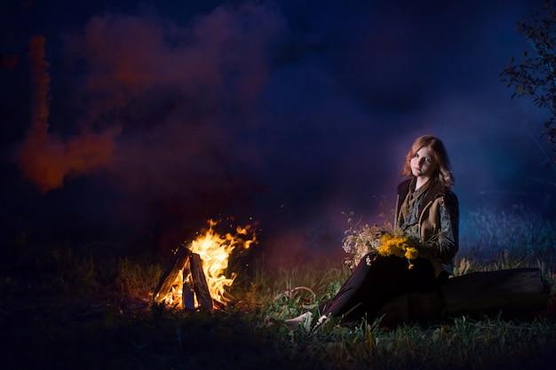 Jovem bruxa pelo fogo da noite na floresta
