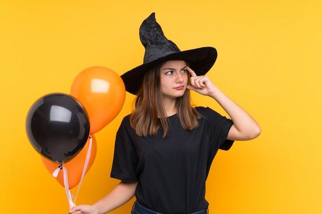 Jovem bruxa segurando balões de ar preto e laranja para festas de halloween com dúvidas e com a expressão do rosto confuso