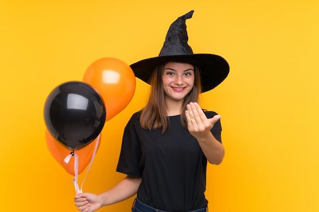 Jovem bruxa segurando balões de ar preto e laranja para festas de halloween, convidando para vir com a mão. feliz que você veio
