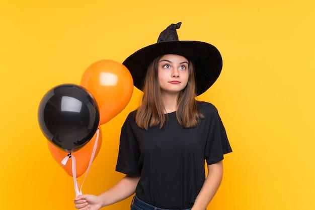 Jovem bruxa segurando balões de ar preto e laranja para festas de halloween, fazendo dúvidas gesto enquanto levanta os ombros