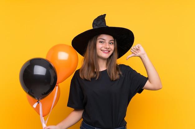 Jovem bruxa segurando balões de ar preto e laranja para festas de halloween, orgulhosa e satisfeita