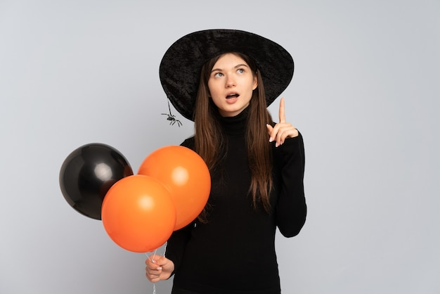 Jovem bruxa segurando balões de ar preto e laranja