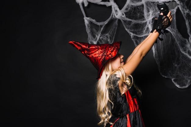 Jovem, bruxa, segurando, morcego brinquedo