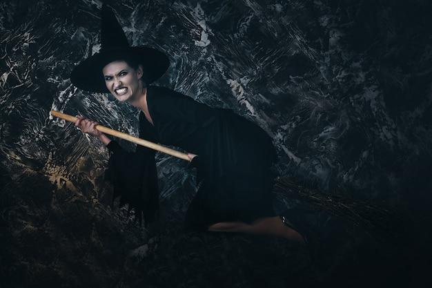 Jovem bruxa voando na vassoura