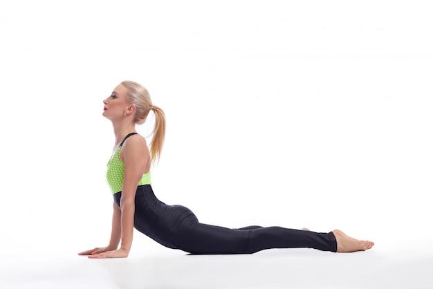 Jovem cabe fêmea praticando ioga, esticando as costas