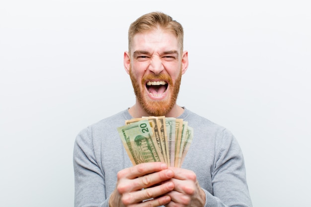Jovem cabeça vermelha com dólares contra o fundo branco