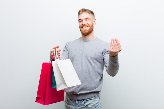 Jovem cabeça vermelha com sacos de compras contra branco