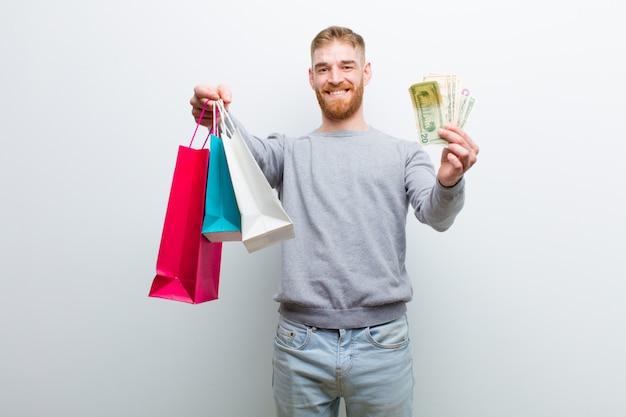 Jovem cabeça vermelha com sacos de compras contra fundo branco
