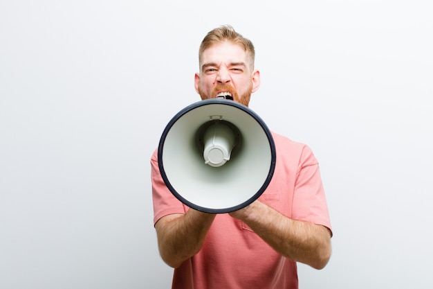 Jovem cabeça vermelha com um megafone contra fundo branco