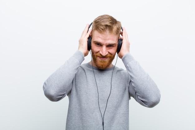 Jovem cabeça vermelha homem ouvindo música com fones de ouvido contra branco