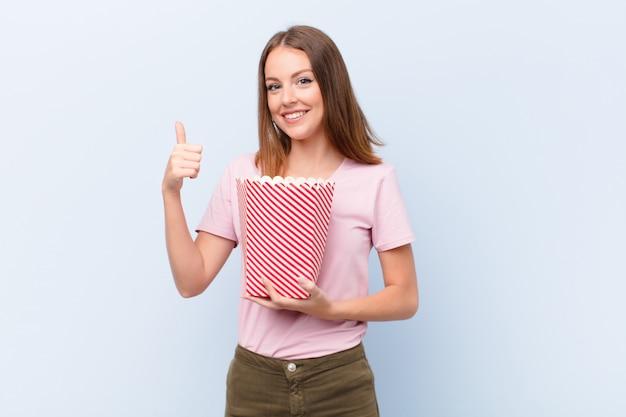 Jovem cabeça vermelha mulher contra uma parede plana com um balde de popconrs