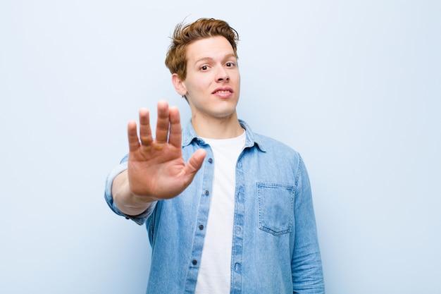 Jovem cabeça vermelha olhando sério, popa, descontente e com raiva mostrando a palma da mão aberta, fazendo o gesto de parada contra a parede azul