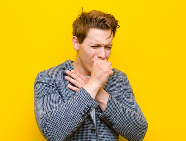 Jovem cabeça vermelha, sentindo-se doente com sintomas de dor de garganta e gripe, tossindo com a boca coberta