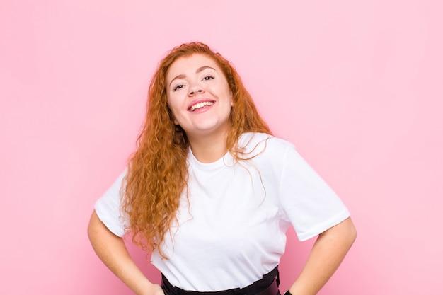 Jovem cabeça vermelha sorrindo alegre e casualmente com uma expressão positiva, feliz, confiante e relaxada contra a parede rosa