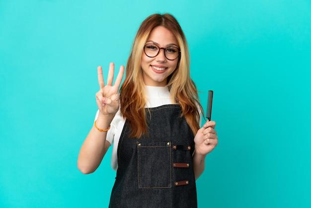 Jovem cabeleireira em um fundo azul isolado feliz e contando três com os dedos