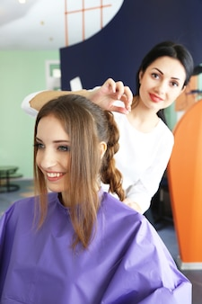 Jovem cabeleireira faz penteado garota em salão de beleza