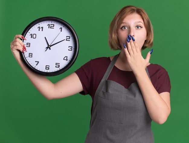 Jovem cabeleireira linda com avental segurando um relógio de parede olhando para a frente espantada e surpresa, cobrindo a boca com a mão em pé sobre a parede verde